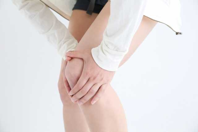 膝を抑える女性