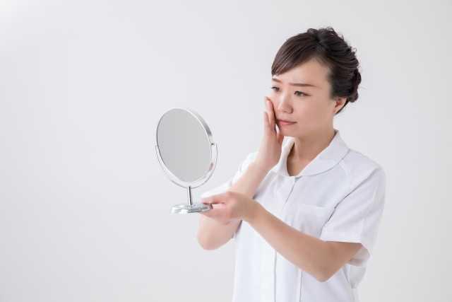 鏡をのぞく女性の画像