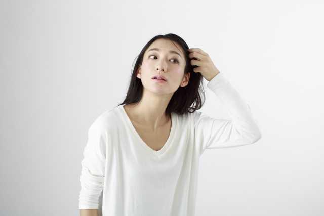 髪の毛を触る女性