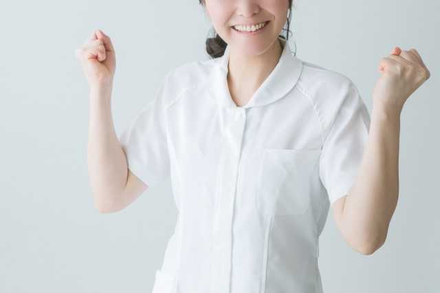 両腕を上げる看護師