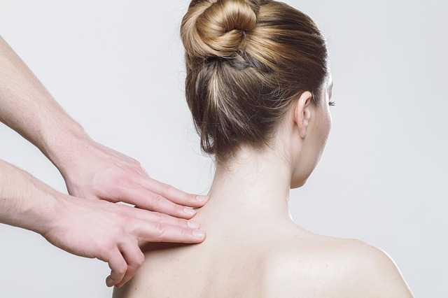 肩をマッサージされる女性